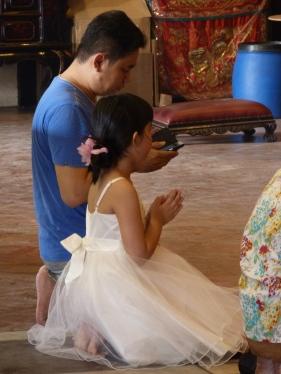 Pare llegint del mòbil la pregària que ha de recitar la filla